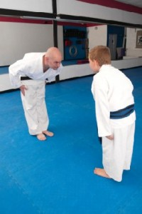 martial art school owner bows to student