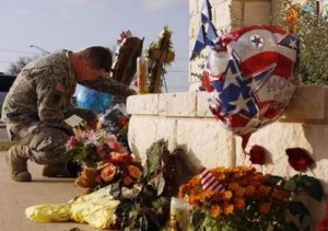 A soldier mourns the victims of the terrorist attack at Ft. Hood, Texas. Reuters